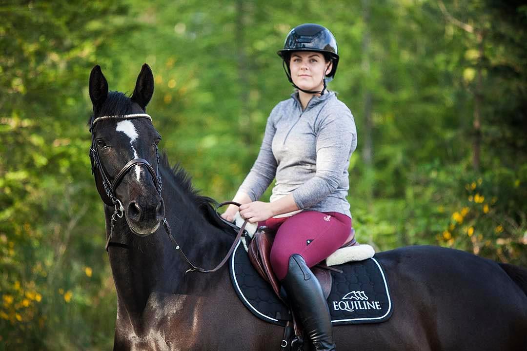 Jørunn sitter på hesteryggen på en sort hest med hvit stripe langs ansiktet. Jørunn har lilla ridebukser og sorte støvler på, hun har en grå genser med glidelås og sort ridehjelm på hodet. Hun ser alvorlig inn i kameraet, hesten ser også mot kameraet.