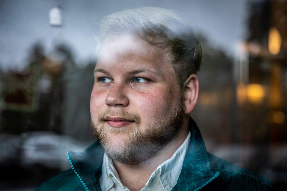 Christer har lys hud, blondt hår, blå øyne og skjegg. Det er et nærbilde av Christer. Han har på seg en grønn ytterjakke og hvit skjorte.