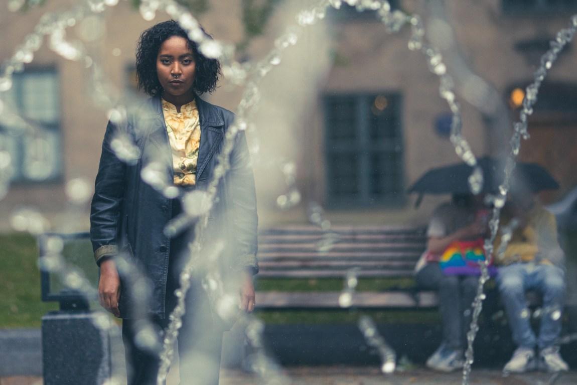 Selena står bak en fontene. Det sitter to stykker bak henne under en paraply. Den ene personen har en regnbuefarget veske på fanget. Det er masse vann foran Selena. Det ser litt ut som et kunstverk.