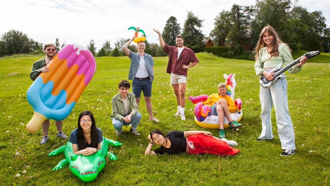 Foto av de 8 som skal lage programmet P3sommer. De smiler. Flere av dem står med fargerike badedyr.