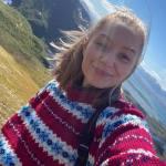 Elise Frantzen Holm ser smilende i kameraet, hun har en rød ullgenser på med blått og hvitt mønster og hun er ute i naturen. Man kan se en gress-slette bak henne og fjell lengre bak.