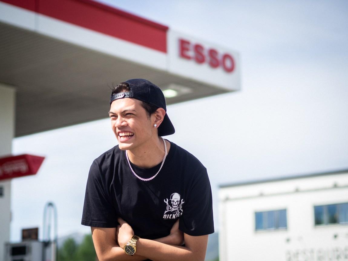 Et bilde av «Kim» (Matthew Santos) som står foran Esso i Bø og ler