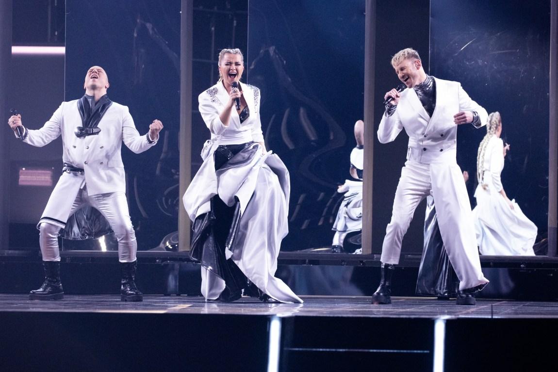 Fred Buljo, Alexandra Rotan og Tom Hugo Hermansen synger av full hals på MGP-scenen. De er alle kledd i hvitt med sorte detaljer. Scenebakgrunnen er også sort.