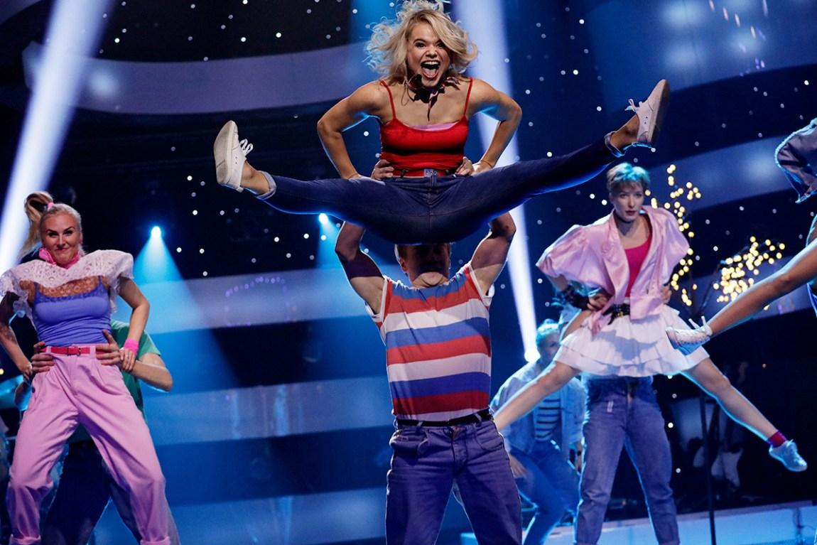 Bilete av ei ung kvinne som blir løfta opp av ein mann med stripete skjorte og i lufta kaster ho beina ut til sida. Ho er blond og har på seg ein raud topp, medan buksa er blå. Ho har på seg kvite sko. Munnen er open.