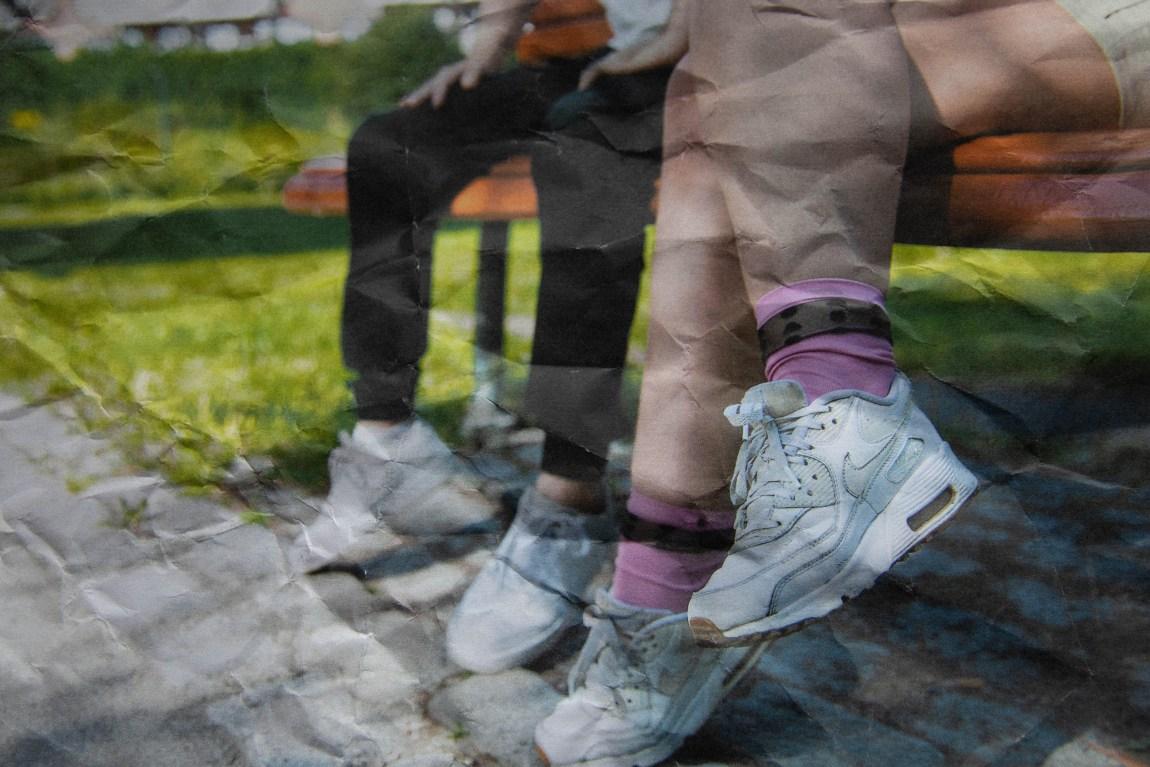 Det er to personer som sitt på ein benk, men vi ser berre føtene. Det eine paret med føtter har på seg rosa sokker og kvite sko. Det andre paret med føtter har på seg svart bukse og kvite joggesko. Bildet er redigert slik at det skal sjå ut som eit knurvet papir.