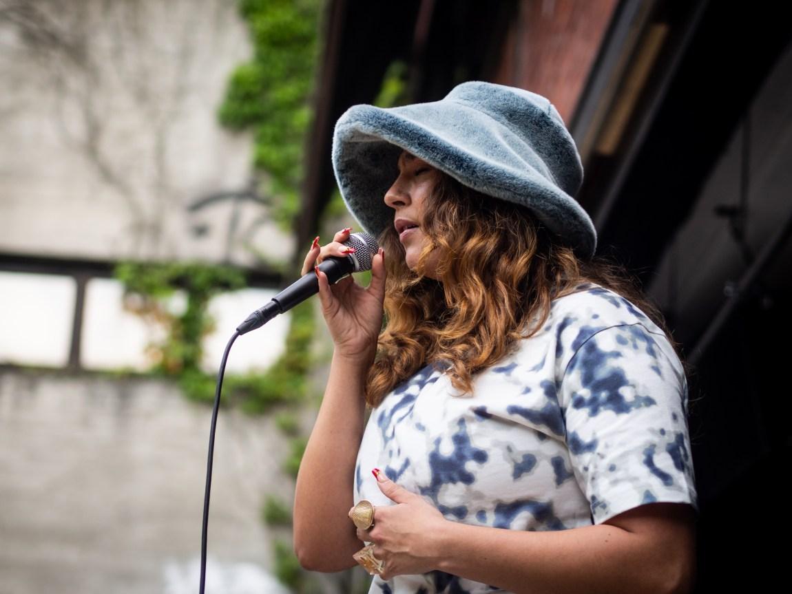 Nærbilde av Nedja i profil fra konserten. Hun har lukkete øyne og synger inn i en mikrofon. Ikledd en stor og lodden blå hatt.