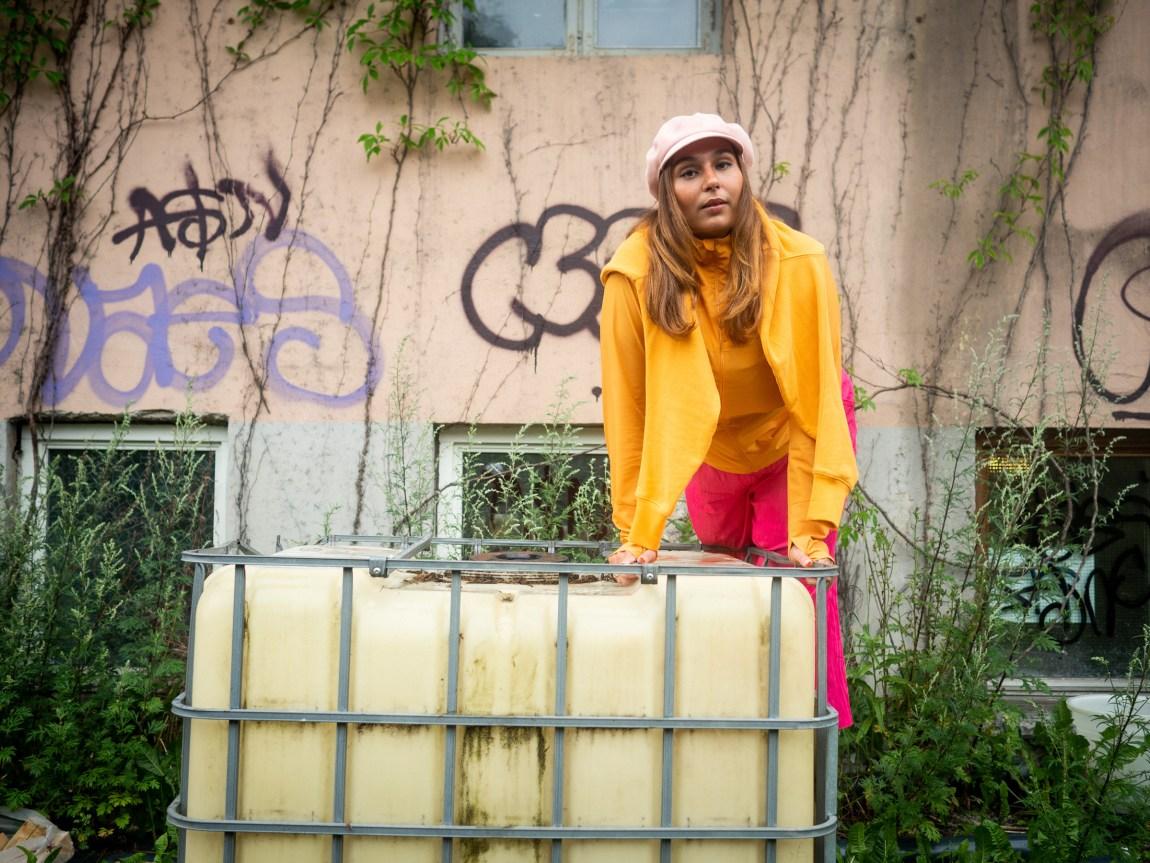 Nedja balanserer lent over en slitt plastboks foran en rosa vegg med klatreplanter og graffiti. Nedja har på seg sterke oransje og rosa klær.