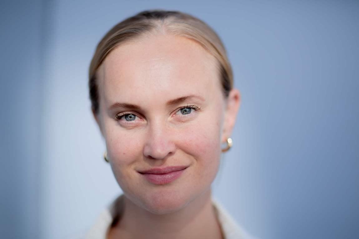 Sofie Frøysaa har stram hestehale, gullringer i ørene og smiler.