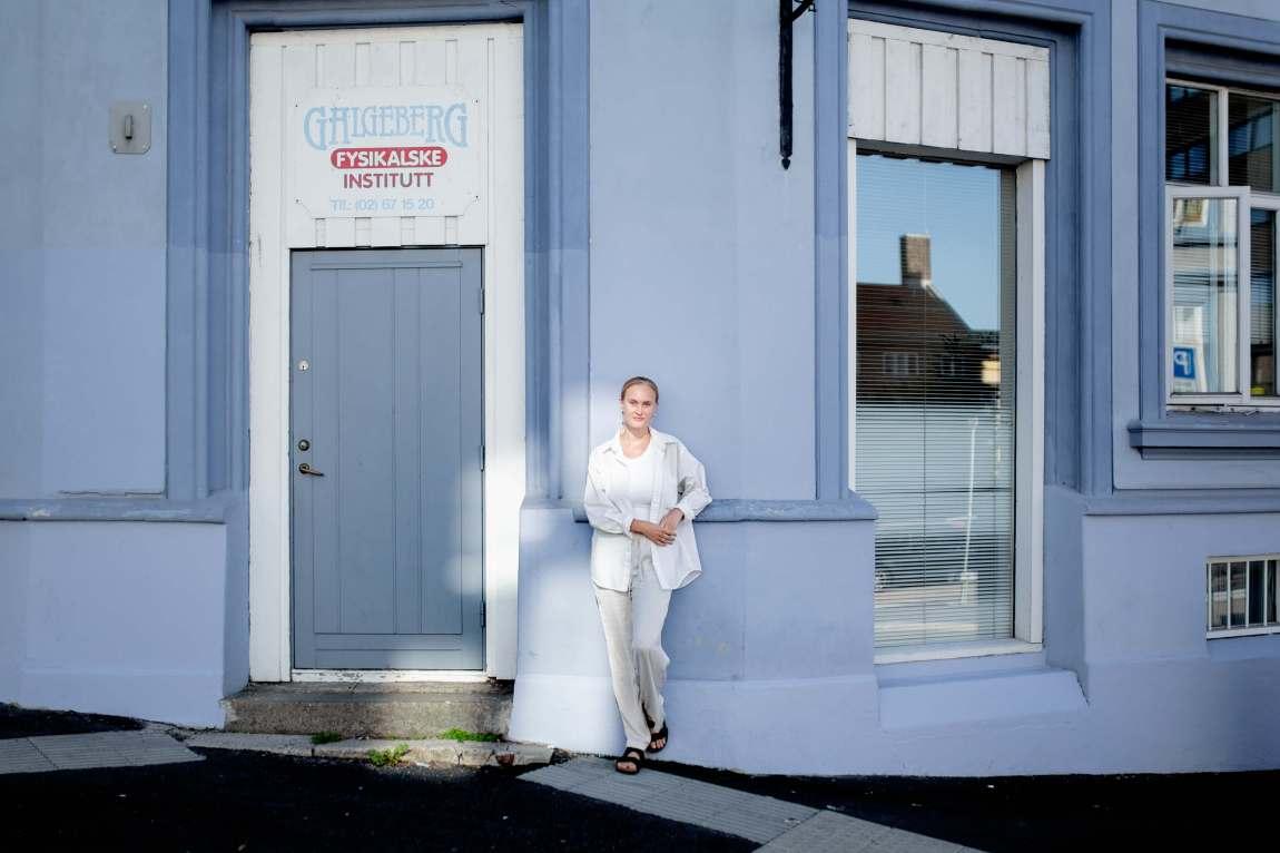 Sofie Frøysaa er innrammet i et lysskjær foran en dus blå mursteinsbygning på Galgeberg. Hun er ikledd hvitt fra topp til tå.