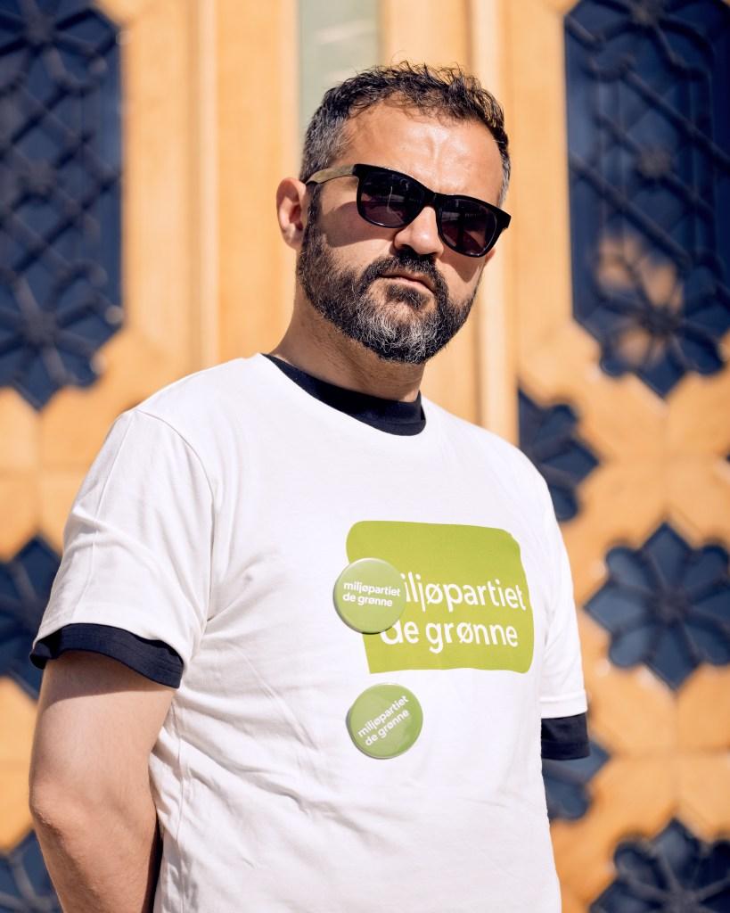 Galvan er iført en hvit T-skjorte med MDG-logo i grønt og har et alvorlig drag over ansiktet.