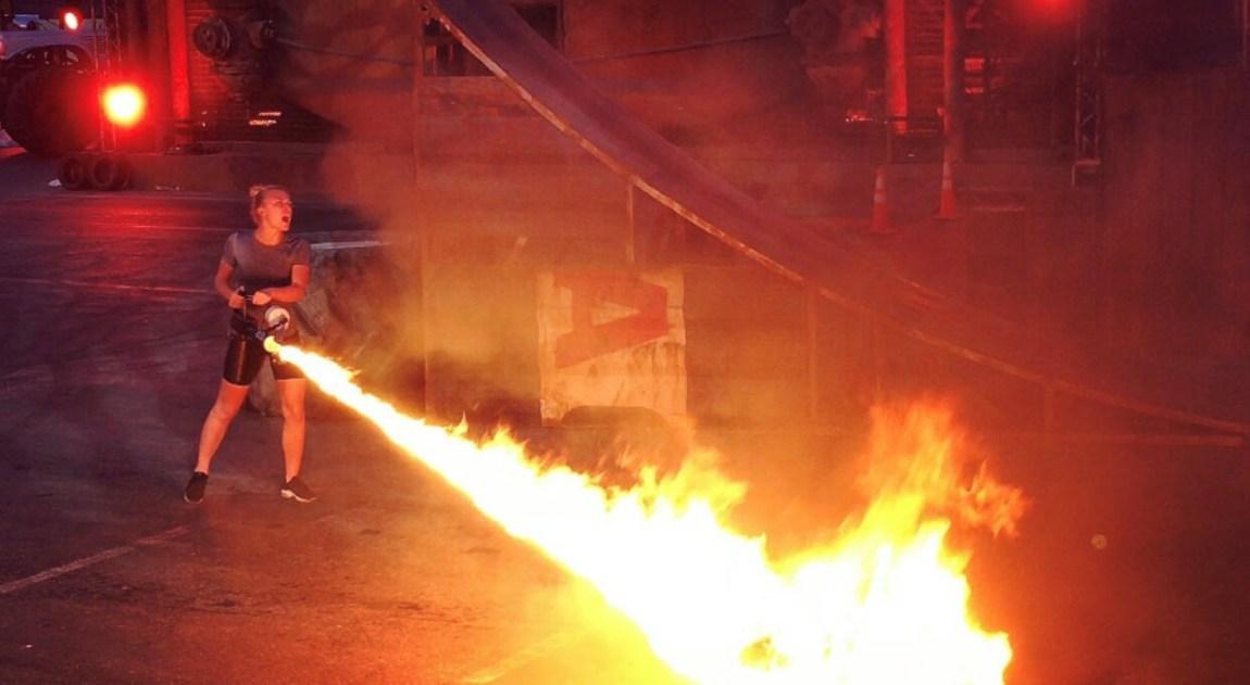 Bilde av Linn Solem som skyter flammer mot bakken. Det ser ut som hun holder en flammepistol, for det er hun som skyter flammene mot bakken..