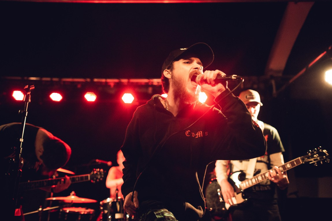 Et bilde av Murmaids vokalist på scenen. Han har på seg sort hettegenser og sort caps