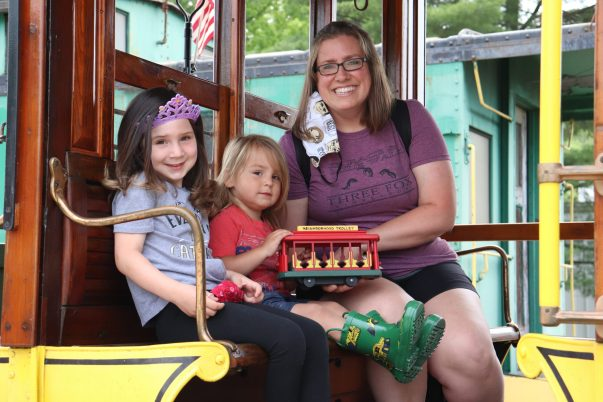 Mother and two daughters sitting on 1758 Open Car. younger daughter holding Mister Rogers red open car trolley