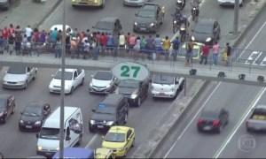 Da passarela da Avenida Brasil, pedestres aguardam a passagem do comboio com Cabral preso - Reprodução de TV