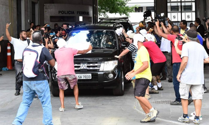 Manifestantes com guardanapos na cabeça acompanham saída de Cabral da PF - TASSO MARCELO / AFP
