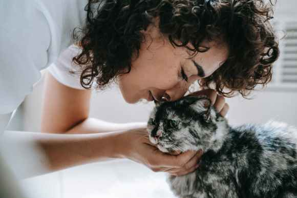 woman touching cat with nose