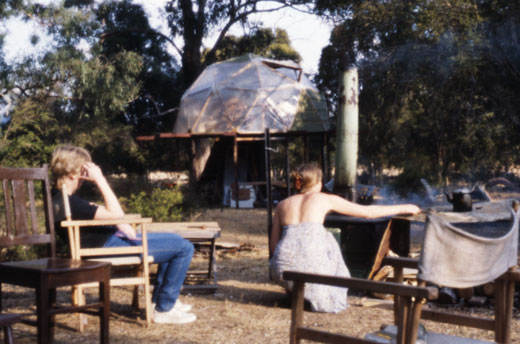 Cooking on the outside fuel stove at Mungay Creek while Fiona takes it easy. Behind is the geodesic dome, at that stage still clad in plastic. Later, a room was added to the right hand side of the structure and the adjoining downstairs room that contained the kitchen enclosed in log offcuts.