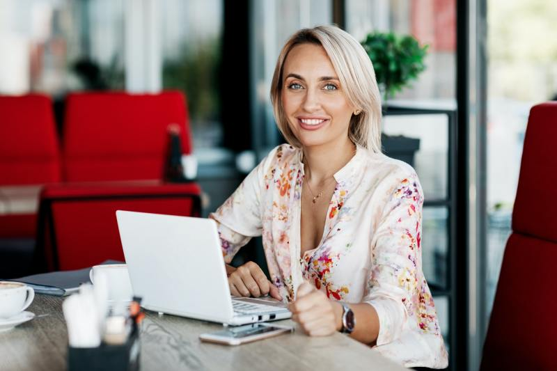 Portrait of a young business woman working at a laptop. Freelancer, business, business online