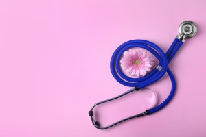 stethoscope and pink flower on pink background. gynecology concept.
