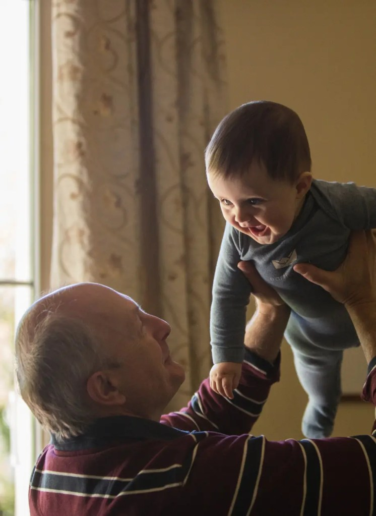 grandfather lifting baby after prp joint injections