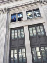 Onlookers cheer on marchers from their office photo credit Jeff B White The Pacific Tribune
