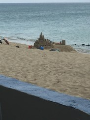 A hotel guest building a sandcastle outside of Sandcastle Hotel