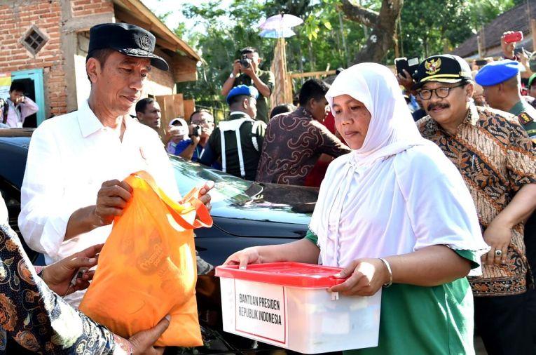 Jokowi memberikan bantuan kepada salah satu ibu korban bencana di Pacitan.