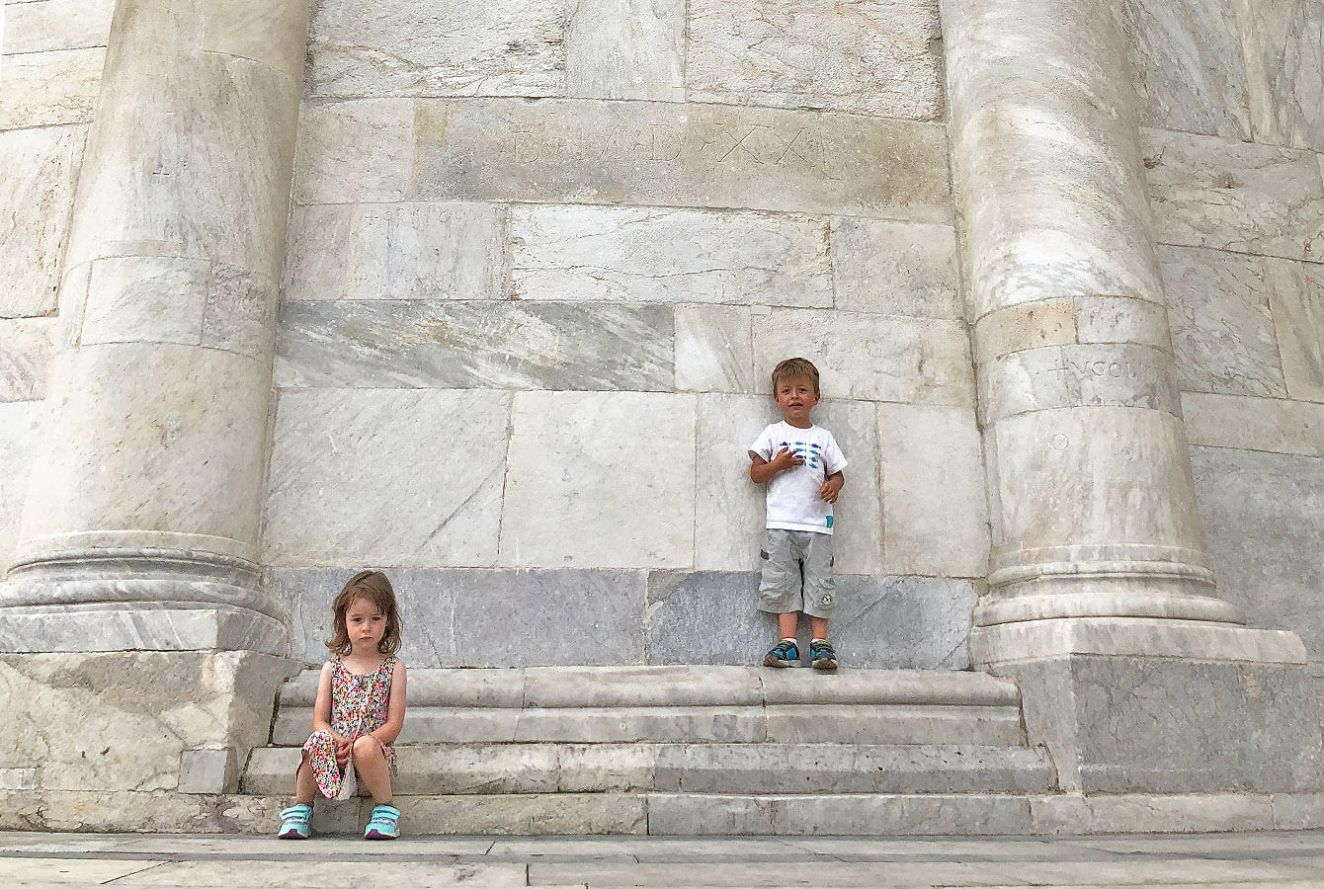 kids standing in front of the Marble wall in Pisa, Italy