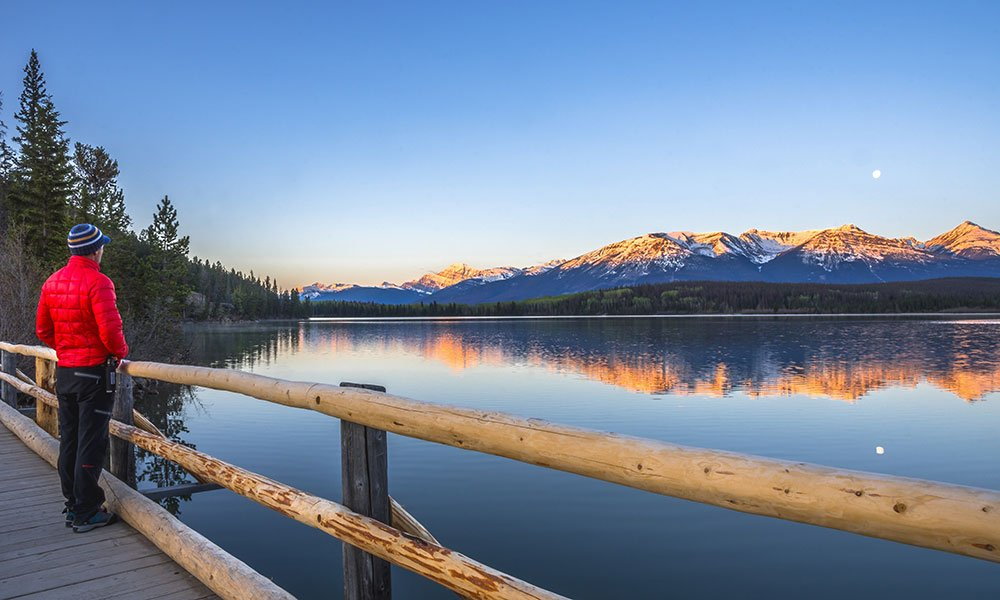 man standing at bridge watching the sunrise at pyramid lake in Jasper