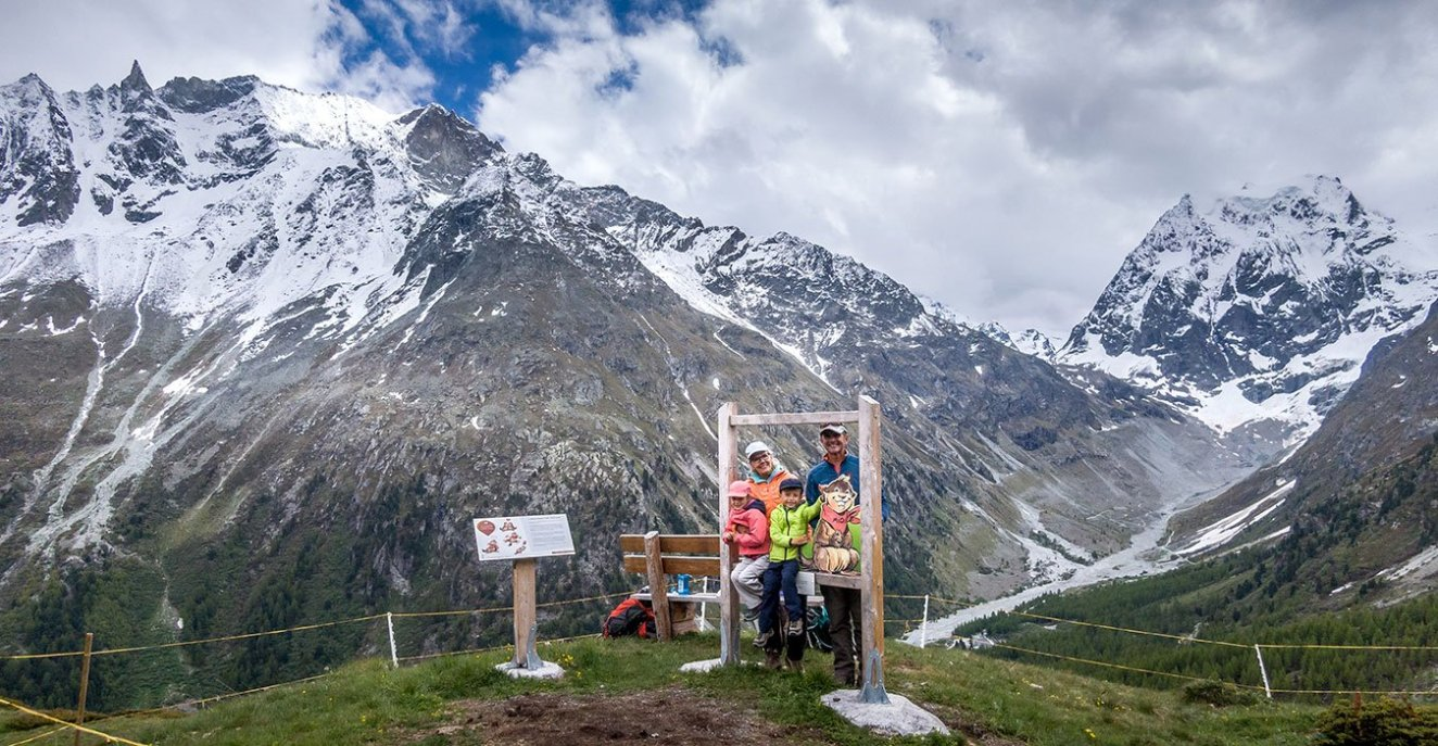 family standing at a photo post on the marmot hike in Arolla