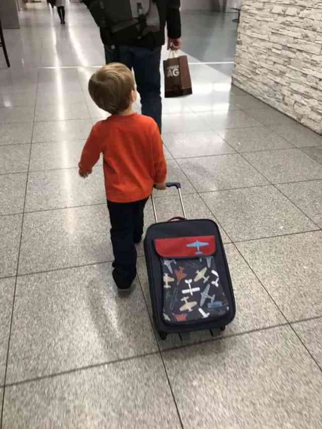 Little boy pulling a suitcase in the airport off to Budapest, Hungary