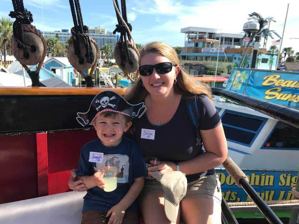 Mother and son sitting on a pirate boat with drinks in hand