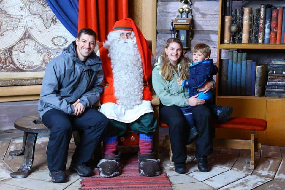 Father, mother and son sitting with Santa