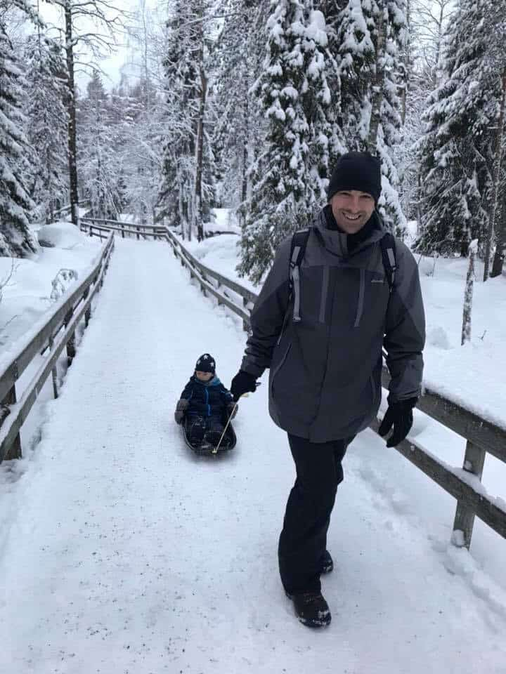 Father pulling son in a sled at the zoo