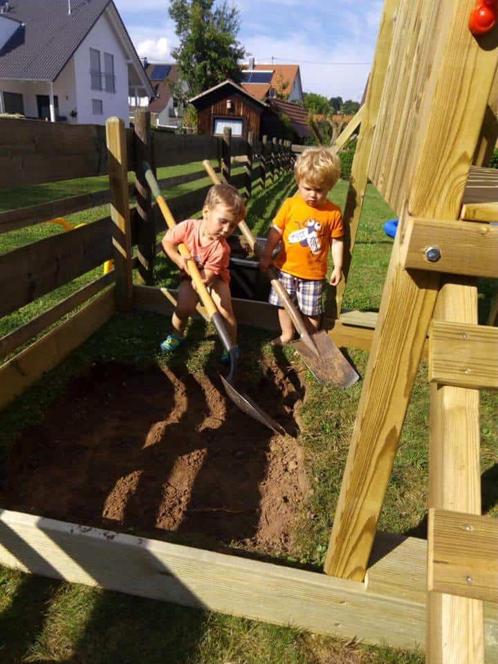Two boys helping to dig out a sandbox in Germany