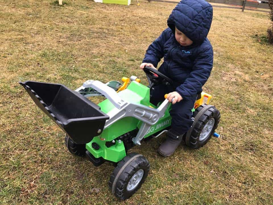 Little boy playing on a kid sized tractor