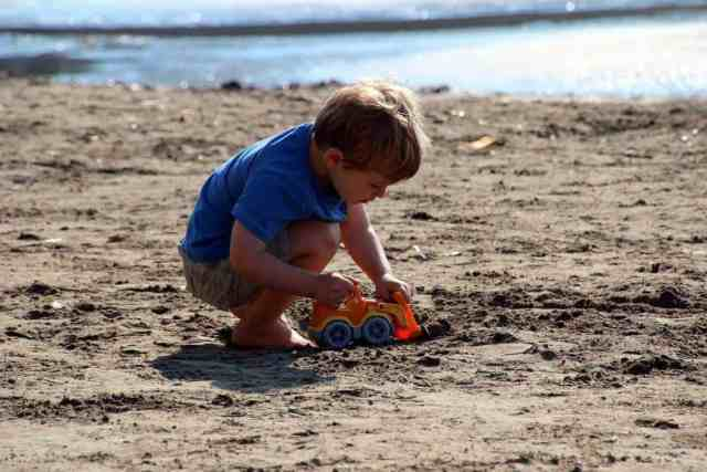 Little boy playing with a bulldozer on the beach in Split, Croatia