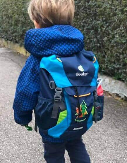 Little boy wearing a child sized backpack while walking to forest preschool.