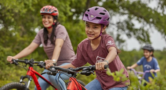 Cub Scouts girls and leader biking