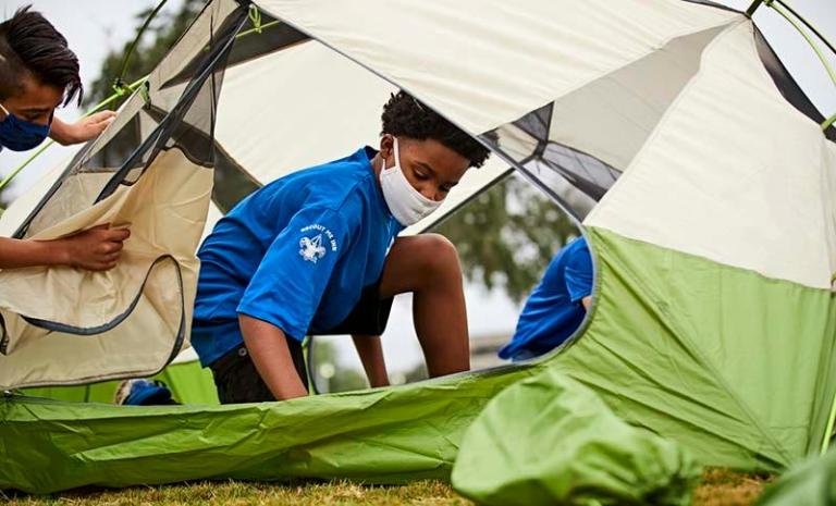 Masked Scouts BSA boys setting up tent
