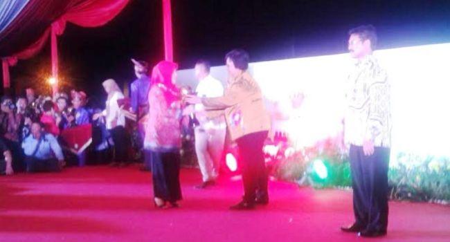 Kepala SDN 21 Taluak Banuhampu Riza Safitri menerima Adiwiyata Mandiri dari Menteri LHK Siti Nurbaya, Jumat (22/7) malam. (ist)