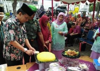 Camat Padang Barat Arfian memotong tumpeng menandai dibukanya lomba tradisional. (der)