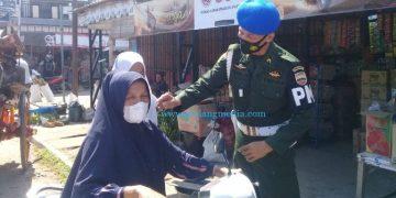 Seorang petugas menunjukkan cara memakai masker yang benar kepada pengendara sepeda motor dalam OY Prokes di Pasar Tarusan, Selasa (15/6/2021). (ist)