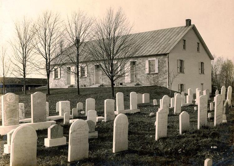 Cemetery in the foreground, church in the background, seperated by trees.