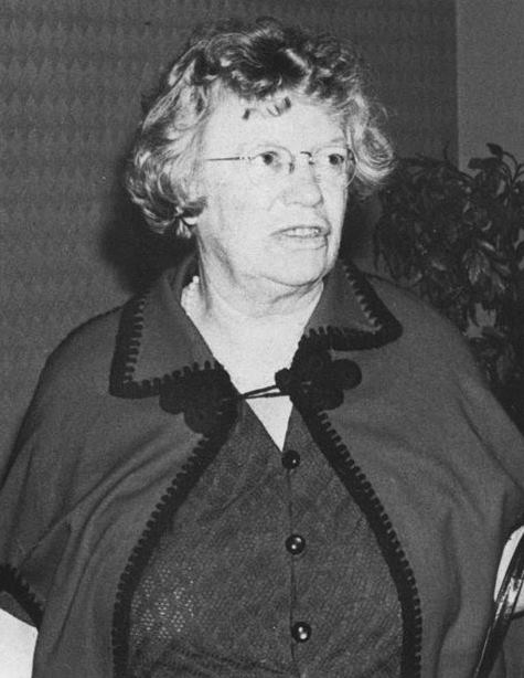 Black and white photo of older white woman with glasses, looking off camera.