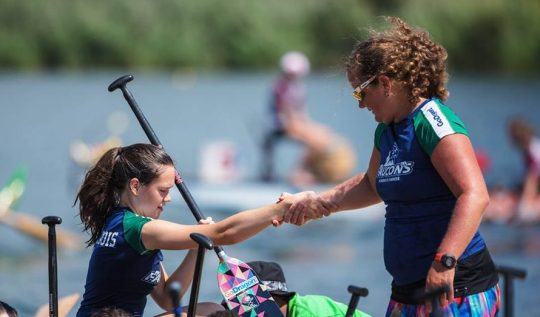 One teammate helping another out of the boat