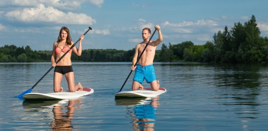 Beginner standup paddleboarders on knees
