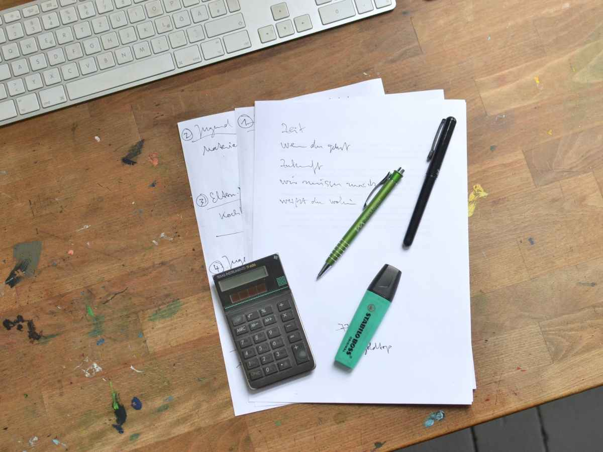 calculator and pens with marker placed on papers