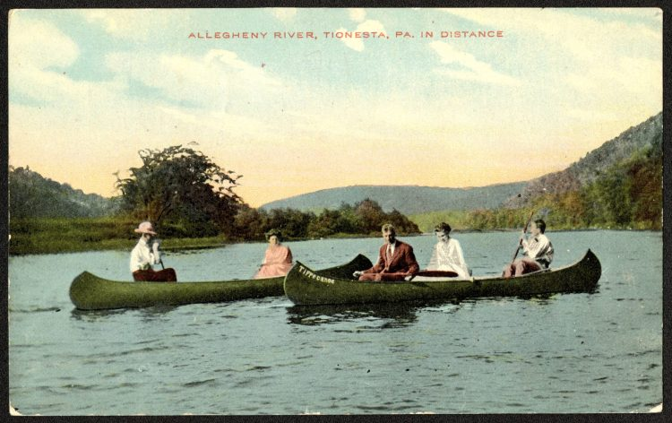 Two canoes with people row on the Allegheny River