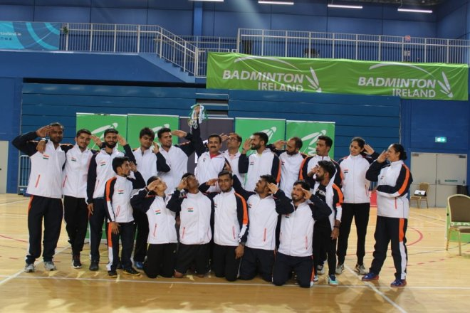 Indian Para badminton players dressed in white and black attire posing for a group photo while their coach Khanna is holding up their medals in a bunch standing in the center of the photograph.